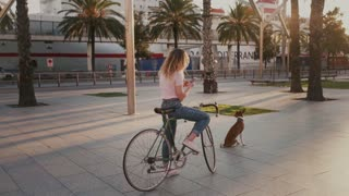 Young woman in casual trendy hipster outfit on bicycle, stopped on sidewalk to talk to friends on messaging smartphone application, uses navigator maps, looks for direction with dog