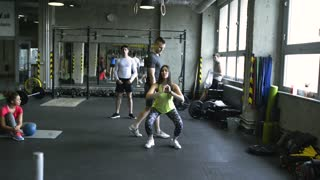 Young woman in crossfit gym with coach doing squats.