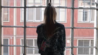 young woman indoors open window and stretching arms