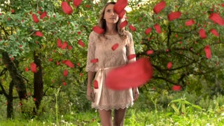 Young woman walking towards camera with red petals falling