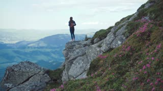 Young woman with a backpack in casual wear stands on the edge of a mountain cliff high above, looks around thrilled. Having fun, adventure time. Hiking alone. Beautiful scenery on the background.