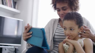 Young woman with a young child laughs as they watch something together on a digital tablet, in slow motion