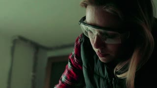 Young woman worker in workroom. Female carpenter using angle grinder. Slow motion