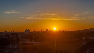 Zoom in towards downtown Los Angeles city skyline as a beautiful sunset transitions into night. Timelapse.