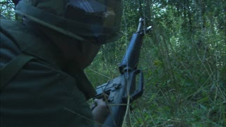 Vietnam Soldier Firing Rifle Into Distant Forest, Close Up