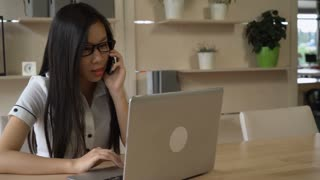 Vietnamese female has phone negotiation with partner explain some point of contract looking to the computer. She typing notes at the laptop. Formal professional young worker at the contemporary office