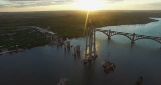 View from drone on building site of bridge over river at sunset