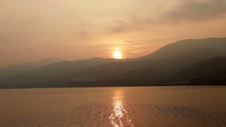View From Water of Sunset Going Behind Mountains in Romania