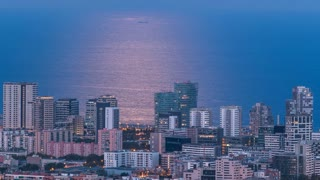 View of Barcelona skyline timelapse with moonpath from full rising moon, the Mediterranean sea and buildings from Bunkers Carmel. Catalonia, Spain. 4K