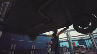View of the interior of a motor workshop looking beneath the undercarriage of a vehicle elevated on a hoist during a service or repair