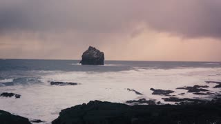 View on rocks on ocean shore Sunset and windy weather Waves beat stones constantly