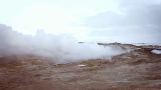 View on the ground with thermal issue Volcanic terrain with smoke rises from underground in winter Car passed by on background