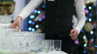 Waiter pouring glasses of champagne at a party or festive occasion with twinkling coloured lights in the background