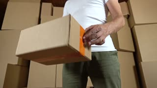 Warehouse worker twisting a small parcel in his hands. Super slow motion shot
