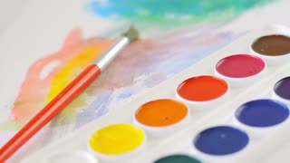 Watercolors, painting and brush on the desk, colorful, expression, calm atmosphere, camera movement