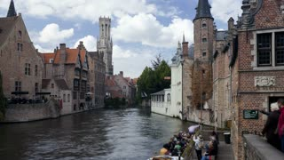 Waterfront buildings and pleasure craft with tourists in the city of Bruges, Belgium, Europe, T/Lapse