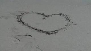 Wave Washing Away Heart In Sand