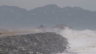 Waves Hitting Rocks Near Roadway in Alaska