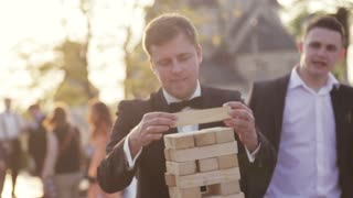 Wedding celebration, a bridegroom in an elegant black wedding costume, white shirt and bow tie playing jenga with his friends during wedding party. Outside shooting, sunset, trees. Wedding atmosphere.