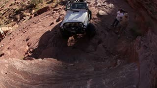 White Jeep Goes Vertical Up Rock Wall