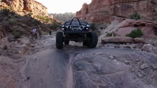 White Jeep Passing by Camera Up Rock Ledges