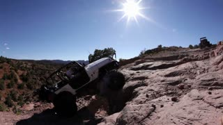 White Jeep Stuck Climbing Steep Ledge