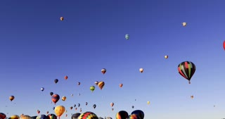 Wide angle shot of hundreds of hot air balloons in deep blue sky