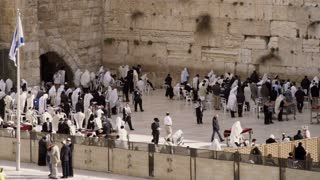 Wide Shot Of Men Praying At Wall