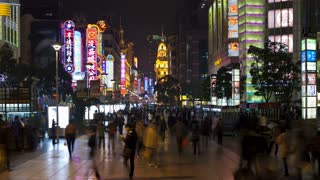 Wide shot of pedestrians walking past stores on Nanjing Road at night, Shanghai, China, Asia, T/Lapse