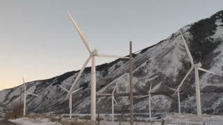 Windmills with snowy mountains in the background