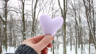 Winter, Love or Valentine's Day idea. Male holding a heart on the background of the winter forest