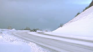Winter Road Traffic on Snowy Highway in the Mountains