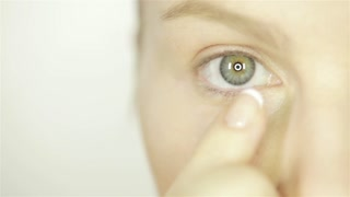 Woman Applying Skin Cream Under Eyes