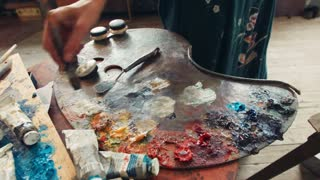 Woman artist mixing oil paint on a palette with a paintbrush from an array of different colored tubes surrounding it, close up of her hand and the art supplies