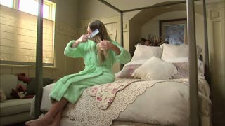 Woman Brushes Her Hair on Bed