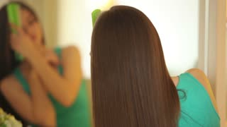 Woman brushing hair and looking at camera with smile. close-up