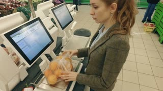Woman buying and weighing the oranges in modern supermarket