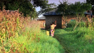 Woman Carries Water and a Child into Village