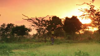 Woman Carries Water at Dawn in Kenya