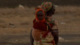 Woman Carrying Child on Her Back in Kenya