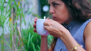 Woman drinking beverage in the street cafe and looking around