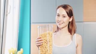Woman eating healthy breakfast cereals with milk and drinking orange juice. Filmed in 4K DCi resolution in Slow motion. Beautiful caucasian woman eating and smiling in the morning in a cozy kitchen.