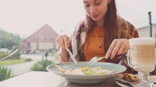Woman eating salad in an outdoor cafe, close up on a plate. 4K Ultra HD, Dolly shot. Healthy lifestyle: young female eating green tasty food and drinking coffee outside. Restaurant terrace.