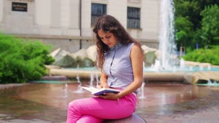 Woman finish reading book and relaxing next to the fountain