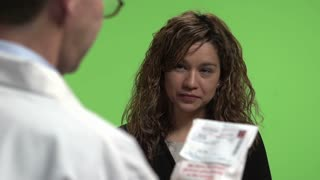 Woman gets a Prescription drug from a pharmacist with the pharmacist explaining about the drug. Shot in front of green screen. Identical shot with pharmacy number 21243086