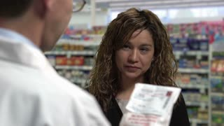 Woman gets a Prescription drug from a pharmacist with the pharmacist explaining about the drug. Shot in front of green screen; Pharmacy added afterwards. Identical shot with green screen number 21244021