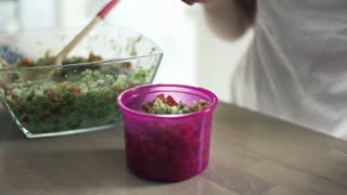 Woman hands closing plastic box with salad in kitchen, slow motion shot at 240fps