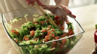 Woman hands mixing salad with wooden spoon in kitchen at home