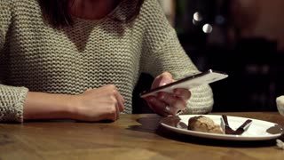 Woman hands texting on smartphone in cafe