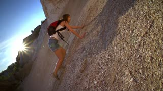 Woman hiking and climbing . Strong determined tourist woman is climbing the rock in sunny mountains. Slow motion filmed at 240 fps.